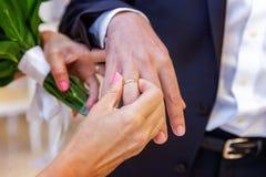 De bruid draagt een ring aan de bruidegom stock afbeelding