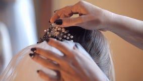 De bruid draagt een sluier bevestigend haar haarspeld Sluit omhoog stock video