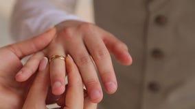 De bruid draagt op de vinger van de bruidegom dichte omhooggaand van de huwelijksslijtage stock videobeelden