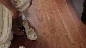 De bruid draagt witte huwelijksschoenen met haar handen stock videobeelden