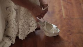 De bruid draagt witte huwelijksschoenen met haar handen stock video