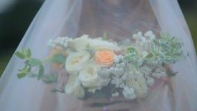 De bruid in een elegante kleding houdt een boeket van bloemen Het koesteren van het lichaam parts stock footage