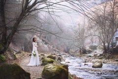 De bruid in een luxueuze witte kleding bevindt zich door de rivier hoog in de bergen Stock Foto's