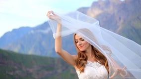 De bruid in een mooie tedere huwelijkskleding houdt een huwelijkssluier stock video