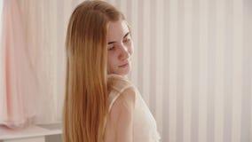 De bruid in een peignoir strijkt haar haar en glimlacht stock footage