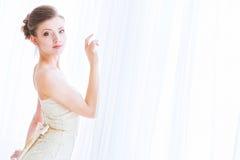 De bruid in een witte kleding over gordijnen. Stock Afbeelding