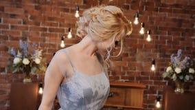 De bruid in elegante huwelijkskleding van sereniteitskleuren spint, glimlachend en stelt voor een camera stock videobeelden