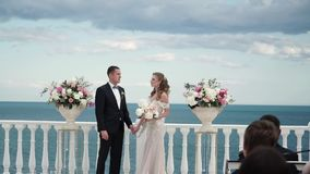 De bruid en de bruidegom bij de huwelijksceremonie Een jong paar in liefde bevindt zich bij de boog Huwelijk door het overzees stock footage