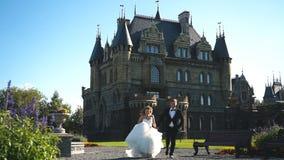 De bruid en de bruidegom die dichtbij het oude kasteel in werking wordt gesteld stock videobeelden