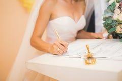 De bruid en de bruidegom die van het huwelijkspaar hun handtekeningen verlaten royalty-vrije stock fotografie