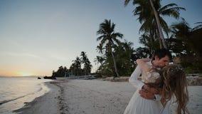 De bruid en de bruidegom door de oceaan Kussen bij zonsondergang op een mooi tropisch strand met palmen Gehuwd romantisch stock video