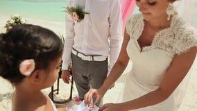De bruid en de bruidegom dragen ringen aan elkaar Huwelijksceremonie bij het strand van de Filippijnen stock footage
