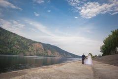 De bruid en de bruidegom hand in hand Stock Foto