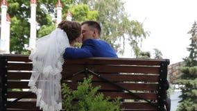 De bruid en de bruidegom in het park op een bank stock videobeelden