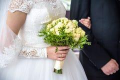 De bruid en de bruidegom houden elkaar ` s tijdens de ceremonie van het kerkhuwelijk overhandigt royalty-vrije stock foto