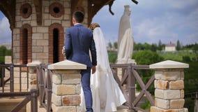De bruid en de bruidegom houden handen lopend langs een oud kasteel met steenstandbeelden stock video