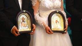 De bruid en de bruidegom houden de pictogrammen in de Kerk tijdens de huwelijksceremonie Sluit omhoog stock video