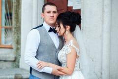 De bruid en de bruidegom koesteren elkaar stock foto