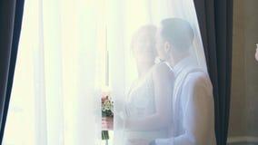 De bruid en de bruidegom kussen achter het gordijn, door het venster stock video