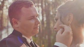 De bruid en de bruidegom in liefde, die elkaar in een mooi groen bos in de zon bekijken Close-upgezichten van jonggehuwden stock video