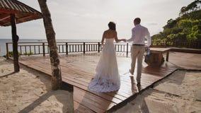 De bruid en de bruidegom lopen samen het houden van handen op het hotel` s terras overziend de oceaan Van de hoogte van stock videobeelden