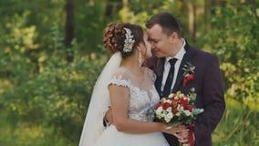 De bruid en de bruidegom met een boeket in het bos de bruidegom koesteren zijn bruid Een zachte kus gelukkig samen Het ogenblik v stock video