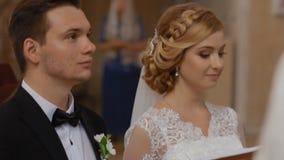De bruid en de bruidegom worden gehuwd in kerk stock footage