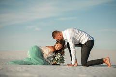 De bruid en de bruidegom zitten blootvoets op wit zand in woestijn, omhelzing en sm Stock Afbeelding
