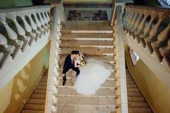 De bruid en de bruidegom zitten op een witte marmeren trap, houden handen en kijken in dezelfde richting stock foto's