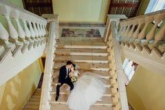 De bruid en de bruidegom zitten op een witte marmeren trap, houden handen en kijken in dezelfde richting royalty-vrije stock fotografie