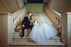 De bruid en de bruidegom zitten op een witte marmeren trap, houden handen en kijken in dezelfde richting royalty-vrije stock afbeelding