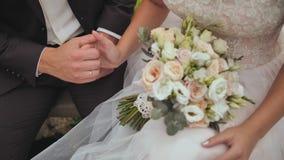 De bruid en de bruidegom zitten en strijken zacht hun handen aan elkaar Close-up van handen en huwelijksboeket stock videobeelden