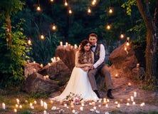 De bruid en bruidegomzitting op de rots Op de achtergrond van ben Stock Foto's
