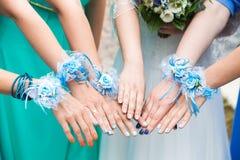 De bruid en de bruidsmeisjes tonen mooie bloemen op hun handen Royalty-vrije Stock Afbeelding