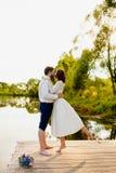 De bruid en de bruidegom bevinden zich op een houten pijler dichtbij de vijver Royalty-vrije Stock Fotografie