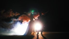 De bruid en de bruidegom bij nacht het kussen en gebruiken de kleurenrook Slow-motion Backlight, stock videobeelden