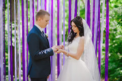 De bruid en de bruidegom dragen elkaar bij een huwelijksceremonie wanneer ringen op een achtergrond van multi-colored linten, lie Royalty-vrije Stock Afbeelding