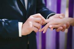 De bruid en de bruidegom dragen elkaar bij een huwelijksceremonie wanneer ringen op een achtergrond van multi-colored linten, lie Royalty-vrije Stock Afbeeldingen