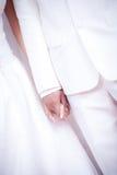 De bruid en de bruidegom dragen witte kleding en de witte handen van de kostuumholding op de ceremonie van de huwelijksdag Stock Foto's