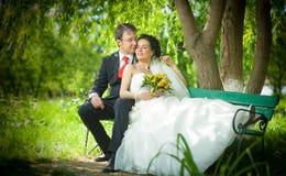 De bruid en de bruidegom in een park zitten op de bank Stock Afbeeldingen