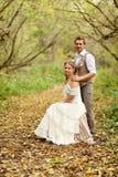 De bruid en de bruidegom in een rustieke stijlzitting bij de herfstbos Royalty-vrije Stock Afbeelding