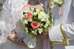 De bruid en de bruidegom houden bruids boeket van rozen Stock Fotografie