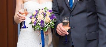 De bruid en de bruidegom houden champagneglazen Royalty-vrije Stock Foto's
