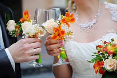 De bruid en de bruidegom houden champagneglazen Stock Foto