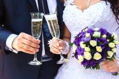 De bruid en de bruidegom houden champagneglazen en een bruids bouqu Stock Foto's