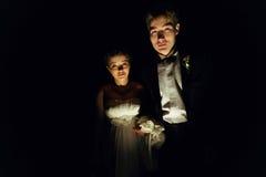 De bruid en de bruidegom kijken geheimzinnige status in de donkere ruimte Royalty-vrije Stock Afbeeldingen