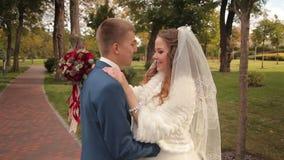 De bruid en de bruidegom lachen en genieten van een gang stock videobeelden