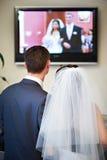 De bruid en de bruidegom letten op de video van zijn huwelijk Stock Afbeeldingen