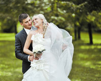 De bruid en de bruidegom omhelzen elkaar en lachend op hun huwelijk Stock Fotografie