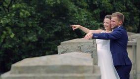 De bruid en de bruidegom onderzoeken de afstand en tonen iets aan elkaar De bruidegom toont aan dat wat stock video